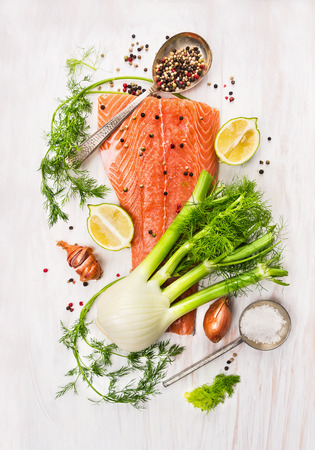 pink salmon: Preparation with raw salmon fillet, fennel, dill, lemon and onion on white wooden background, top view Stock Photo