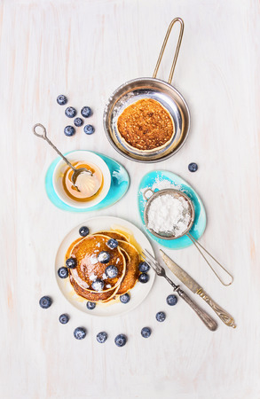 Pancakes with honey and blueberries on white wooden background, top view
