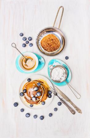 Pannekoeken met honing en bosbessen op witte houten achtergrond, bovenaanzicht