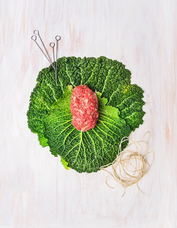 Meat stuffed cabbage leaves on filling, preparation on white wooden table, top view photo