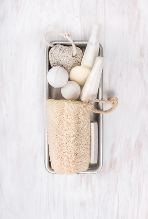 stone volcanic stones: White spa bathroom set with natural loofah sponge in metal box on white wooden background
