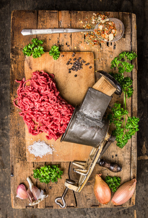 mincemeat: Mincemeat of vintage meat grinder on old wooden table with herbs and spices in spoon, top view Stock Photo
