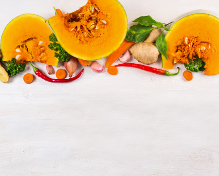fresh ginger: Cutting pumpkin with herbs and spices for soup, food background top view. Stock Photo