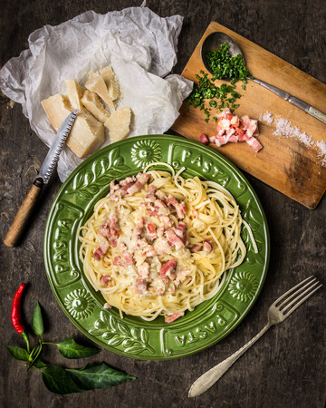 overlook: Pasta carbonara in greenplate, parmesan, spices and seasonings on dark wooden background Stock Photo