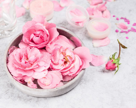 pink roses in gray ceramic bowl of water on gray marble table, cream and candle in jar