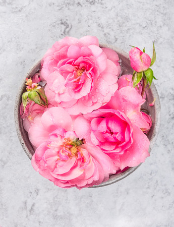 stone bowl: bowl with pink roses and water on gray marble table, spa background