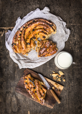 plait: Braided Sweet cake with raisins and almonds cut to pieces in white paper, cup of milk on dark wooden background