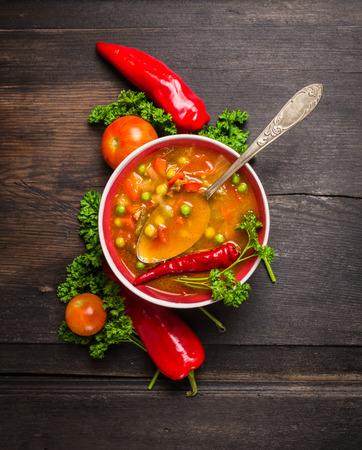 minestrone soep op een donkere houten tafel met vintage lepel en groenten, bovenaanzicht Stockfoto