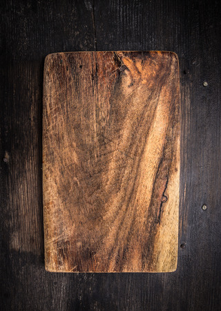 empty board: Old dark cutting board on brown wooden table, background Stock Photo