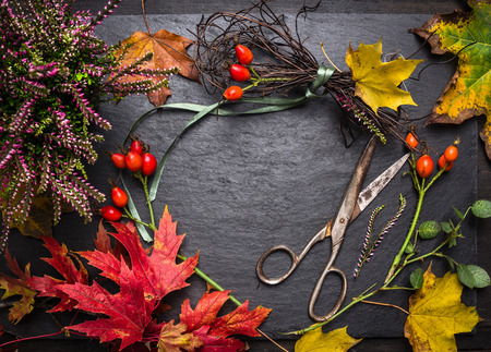 Florist table for Making autumn decorations with leafs, shears and ribbon, fall background with copyspace