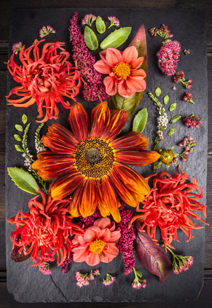 bunch of: autumn flowers composition with sunflower, dahlias and herbs on dark table, floral background Stock Photo