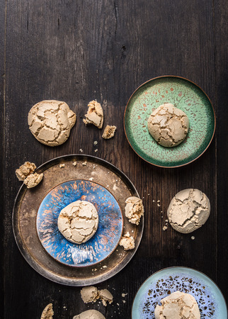 biscuit factory: Cookies with cracks in enameling bowls on dark wooden table Stock Photo