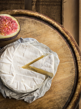 white cheese: Camembert cheese on old wooden board, top view