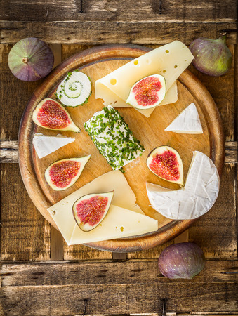 Round gutting board with cheese and figs, top view