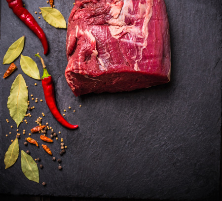 dark meat: raw beef meat fillet with spices on black slate, food background, top view
