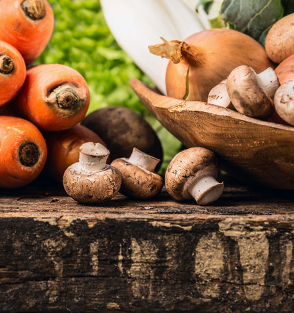 agaricus: Field mushroom and vegetables on old dark wooden table Stock Photo