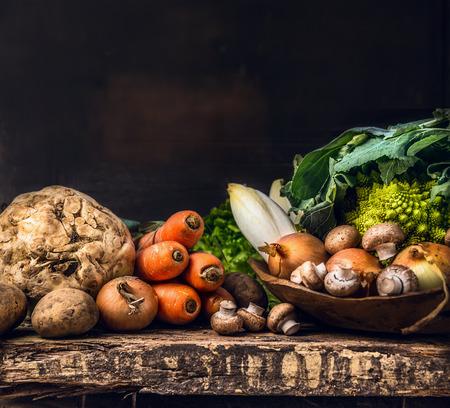 오래 된 어두운 나무 테이블에 원시 야채와 필드 버섯의 다양한 스톡 콘텐츠