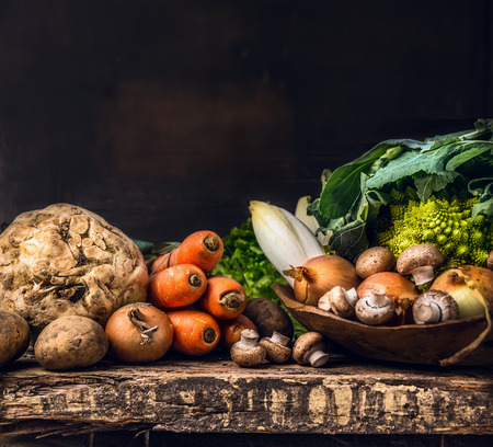 wooden crate: various of raw vegetables and field mushroom on old dark wooden table Stock Photo