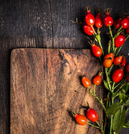 Rosehips on old wooden board, top view, autumn background with copy space