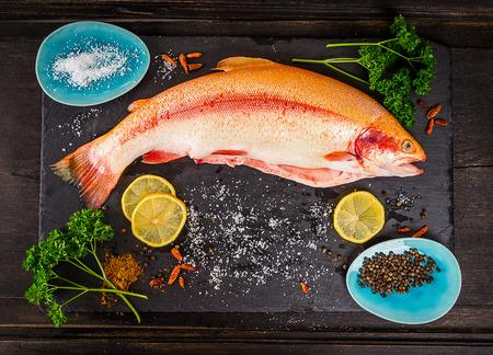 暗い木製のテーブル、準備のスパイスと新鮮なニジマスの魚