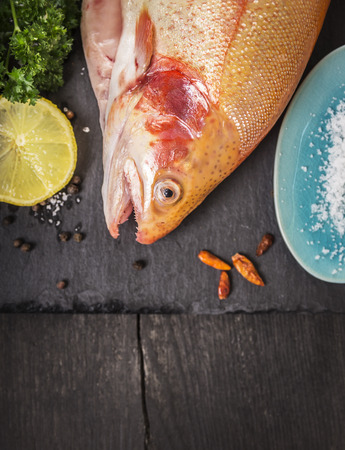 rainbow fish: raw rainbow trout fish on old wooden table with lemon and spices