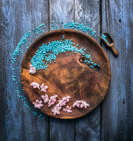 rustical wooden bowl with sea salt, scoop and flowers on blue table, wellness background, top view, copy space photo
