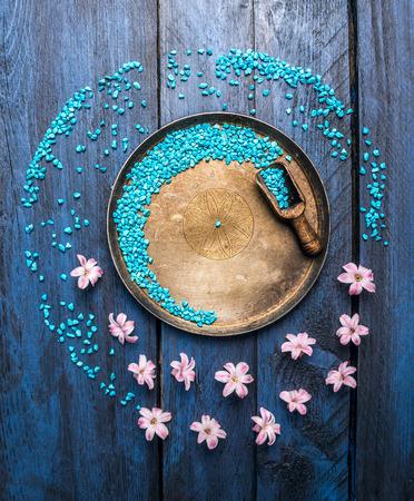 바다 소금과 금속 그릇, 국자와 푸른 나무 테이블, 웰빙 배경, 탑 뷰, 꽃 복사 공간