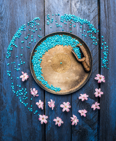metallic bowl with sea salt, scoop and flowers on blue wooden table, wellness background, top view, copy space