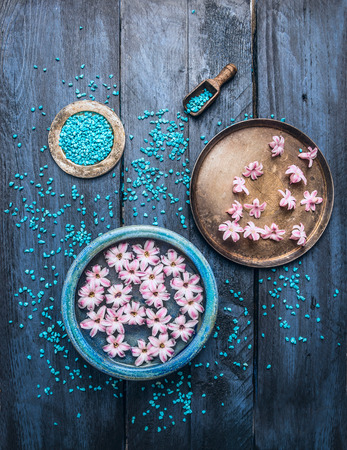 wooden table top view: three bowls with flowers, sea salt and scoop on blue wooden table, wellness background, top view