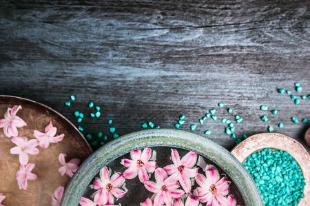 木製のテーブル、ウェルネス背景、上面図、テキストのための場所の青い海の塩および水の鉢にピンクの花