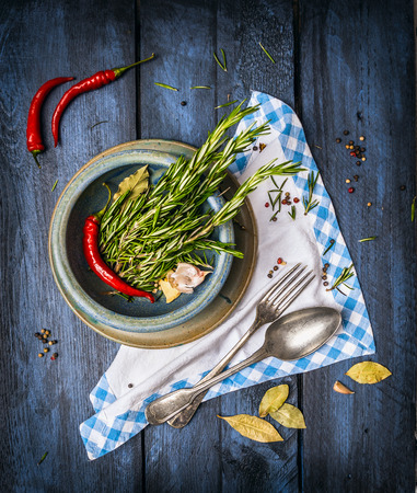 rosemary and spaces in blue bowl on napkin with fork and spoon, blue wooden background, top view photo