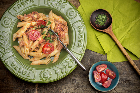 penne pasta with tuna sauce and tomatoes in green plate on old wooden table photo