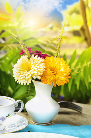 Vase of flowers on tea table in sunny garden. photo