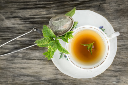 mint leaves: Cup of tea with mint and tea strainer on old wooden table, top view