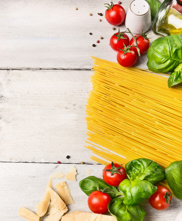 spaghetti ingredients for cooking witj oil,tomatoes and basil on white wooden background, top view photo