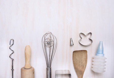 moldy: Baking tools set utensils with rolling pin, spatula, whisk, slotted wooden spoon on white wooden background, top view, place for text Stock Photo