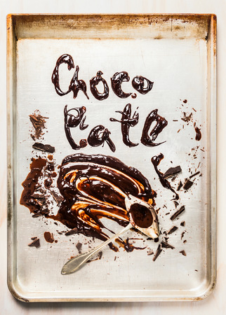 grease paint: Word made with  liquid chocolate on bake tray, top view