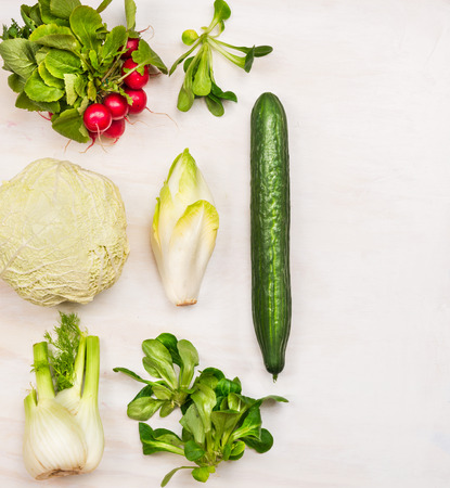 Ingredients for vegetables salad on white wooden background, top view