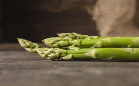 Green asparagus on old wooden background, side view