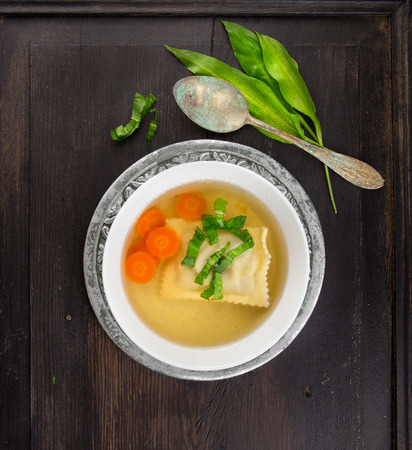 clear soup with German ravioli,carrots and ramson in silver plate with vintage spoon on dark wooden table photo