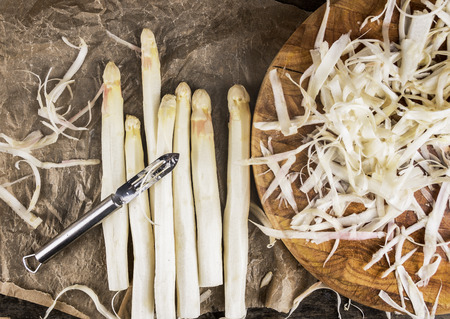 Shelled white asparagus with peelings on brown crumpled paper