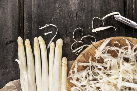 Shelled white asparagus with peelings on dark wooden table