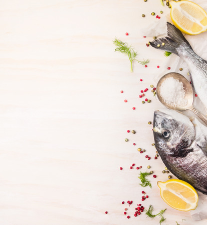 El pescado crudo dorado con pimienta multicolor, limón en la cuchara de sal en el fondo blanco de madera, vista desde arriba, el lugar de texto Foto de archivo - 37810796