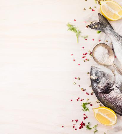 Rauwe dorado vis met veelkleurige peper, citroen op lepel zout op witte houten achtergrond, bovenaanzicht, plaats voor tekst