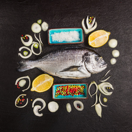 composing: Composing with dorado raw fish, lemon and spices on black textured background, top view