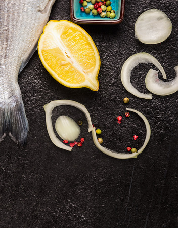 fish tail: Raw fish tail with lemon and spices on black textured background, top view Stock Photo