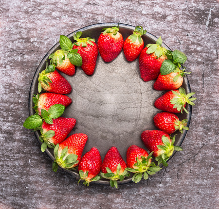 Fresh ripe strawberries in plate on gray wooden background, food frame, top view with place for text photo