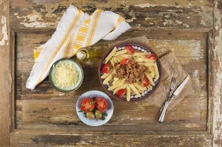 antik: penne pasta with bolognese sauce, bowls of snacks on old wooden table , top view Stock Photo