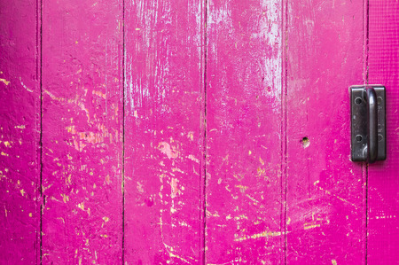 tiled wall: Pink old wooden door scarred with black handle ,background