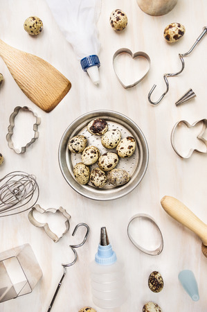 quail eggs in metallic bowl and easter baking tools on white wooden background, top view photo
